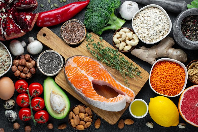 Zdrowy karmowy czysty łasowanie wybór: ryba, owoc, dokrętki, warzywo, ziarna, superfood, zboża, liścia warzywo na czerń betonie fotografia royalty free