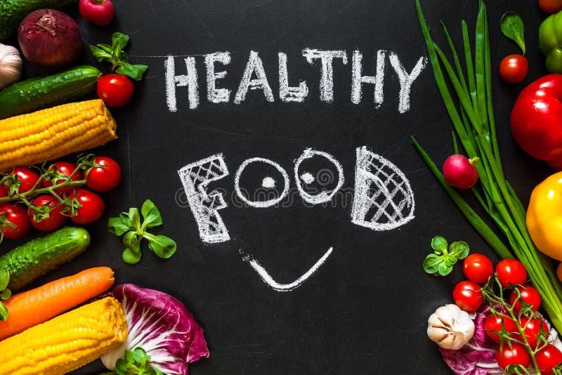 Zdrowy karmowy pojęcie z świeżymi warzywami dla gotować Tytułowego ` Zdrowy karmowy ` z uśmiechem napisze kredą na tle zdjęcia stock