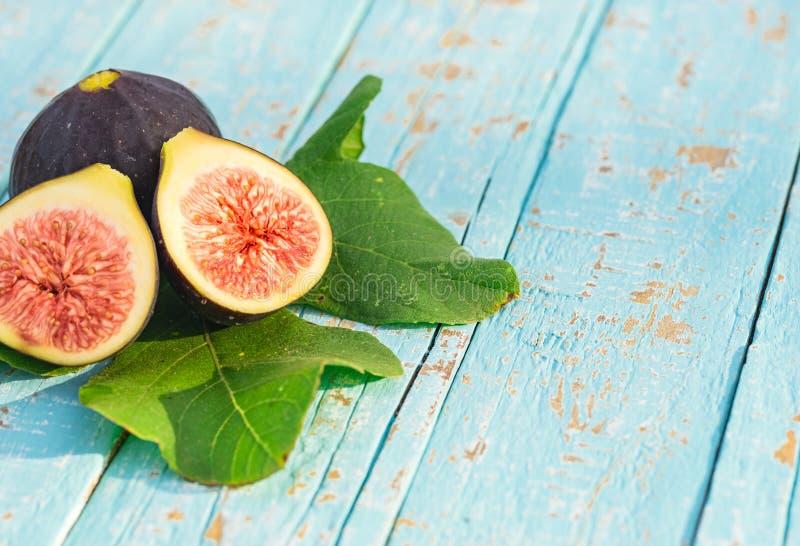 Zdrowy karmowy tło, dojrzałe pokrojone figi z liściem na nieociosanym kuchennym stole zdjęcie royalty free