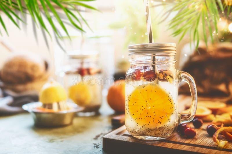 Zdrowy lato napój z Chia sia detox wodę, pomarańczowe owoc plasterek, cytryna sok i cranberries w kamieniarza słoju z dalej, zdjęcie stock