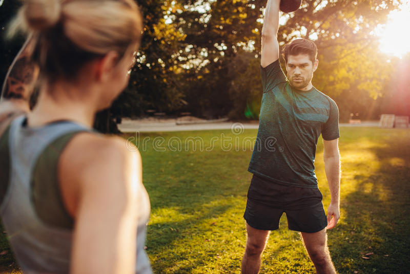 Zdrowy mężczyzna ćwiczy z osobistym trenerem w parku fotografia stock