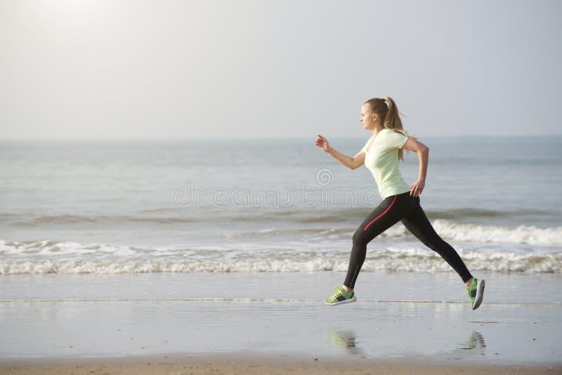 Zdrowy młoda kobieta bieg plażą obraz royalty free