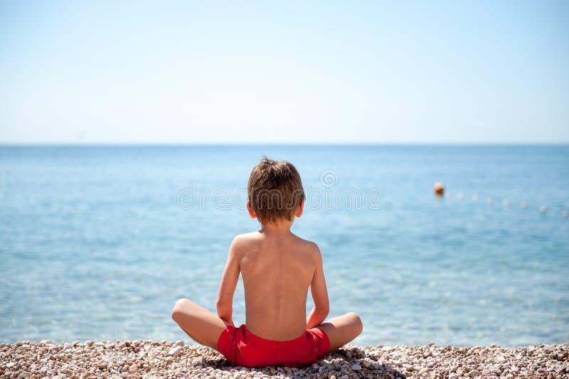 Zdrowy małego dziecka obsiadanie na dennego brzeg plaży dopatrywaniu przy horyzont medytacją obraz royalty free