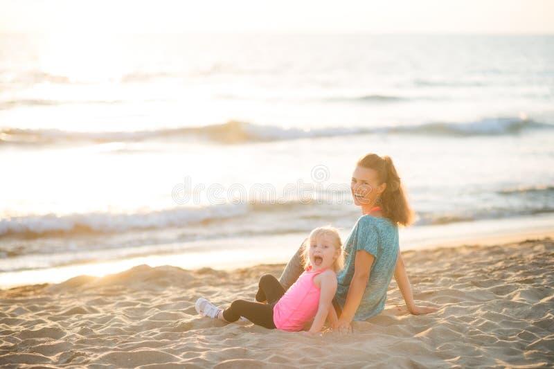 Zdrowy matki i dziewczynki obsiadanie na plaży obrazy royalty free