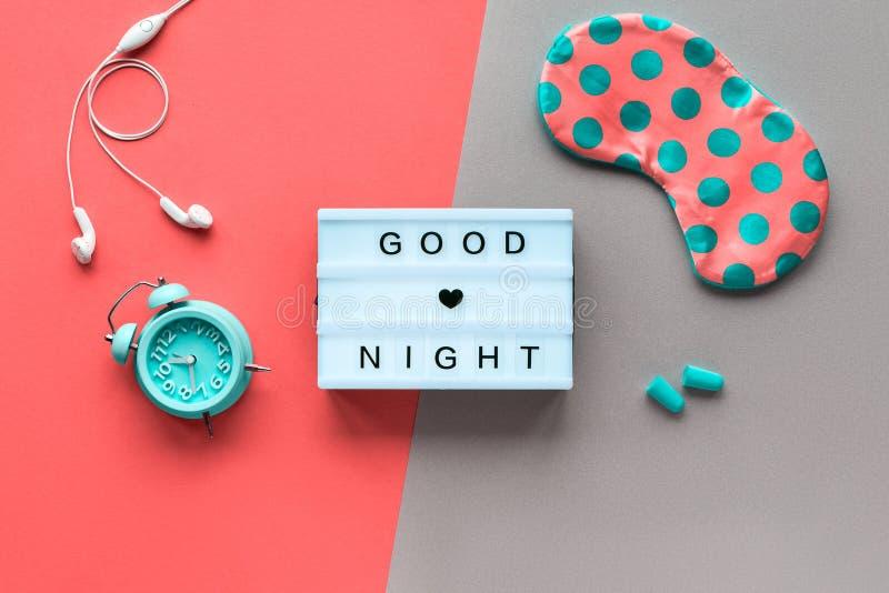 Zdrowy nocny sen kreatywna koncepcja Maska śpiąca w kropkach polki, mały budzik, słuchawki i zatyczki do uszu zdjęcia royalty free