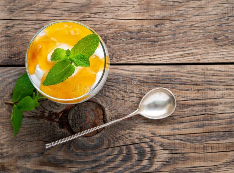 Zdrowy płatowaty deser z jogurtem, banan, mango, krakers na drewnianym tle, odgórny widok fotografia royalty free