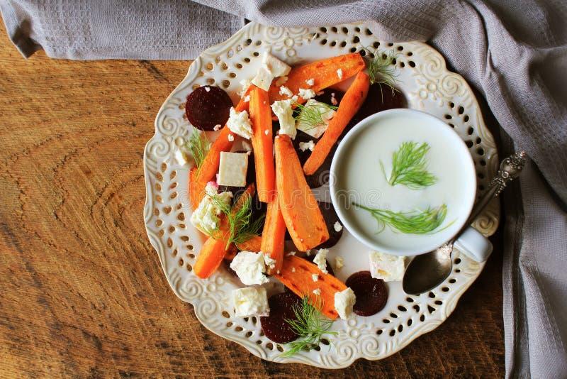 Zdrowy piec na grillu burak, marchewki sałatkowe z serowym feta, koper i grka jogurt w małych szklanych pucharach na wieśniaku dr zdjęcia stock
