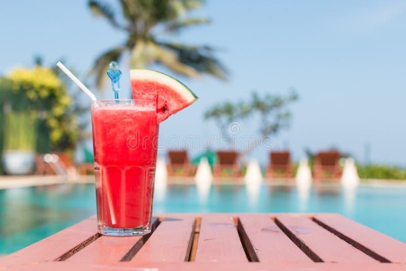 Zdrowy pojęcie, Wodny melonowy smoothie na drewnianym stole z tłem, pływackiego basenu i niebieskiego nieba zdjęcia stock