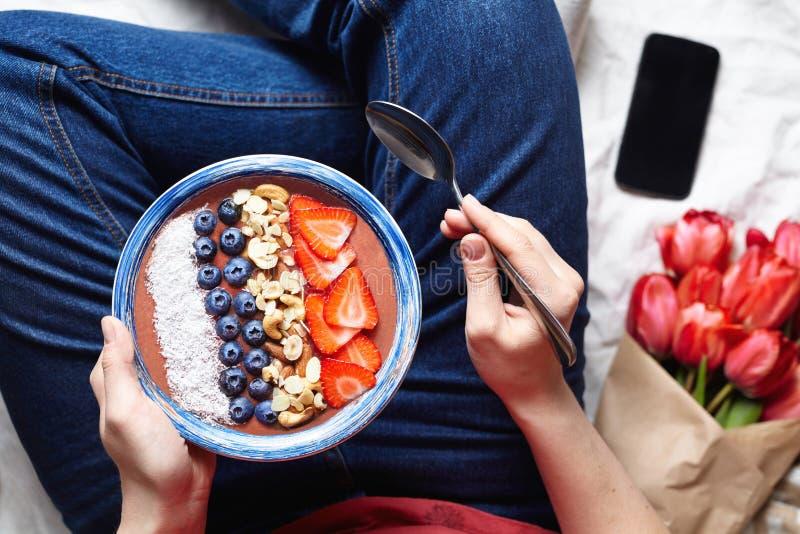 Zdrowy romantyczny śniadanie: puchar smoothies w kobiety ` s rękach w cajgach, bukiet kwiaty i telefon na, obrazy stock