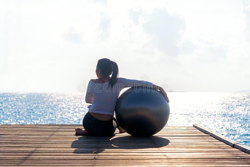 Zdrowy styl życia balansuję kobiety joga balowy ćwiczyć medytuje i energia na moscie w ranku seashore obraz stock