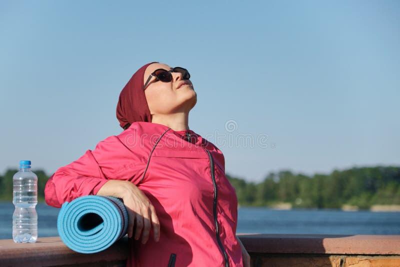 Zdrowy styl życia dojrzała kobieta, plenerowy portret pełnoletnia kobieta w sportswear z joga matą i butelka woda, obraz royalty free