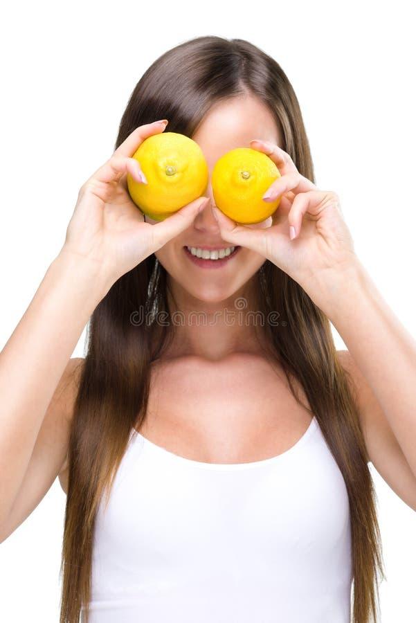 Zdrowy styl życia - Fitt kobieta przed oczami dwa cytryny, zdjęcia royalty free