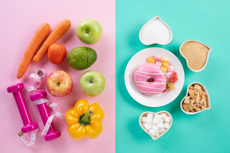 Zdrowy styl życia, jedzenie i sporta pojęcie, Odgórny widok zdrowy versus niezdrowy Pączek i różnorodni typy cukier VS owoc obrazy royalty free
