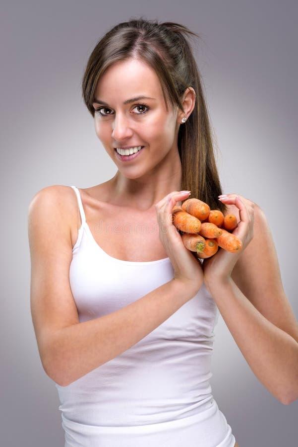 Zdrowy styl życia! Piękna kobieta trzyma udziały marchewka kierowy kształt zdjęcia royalty free