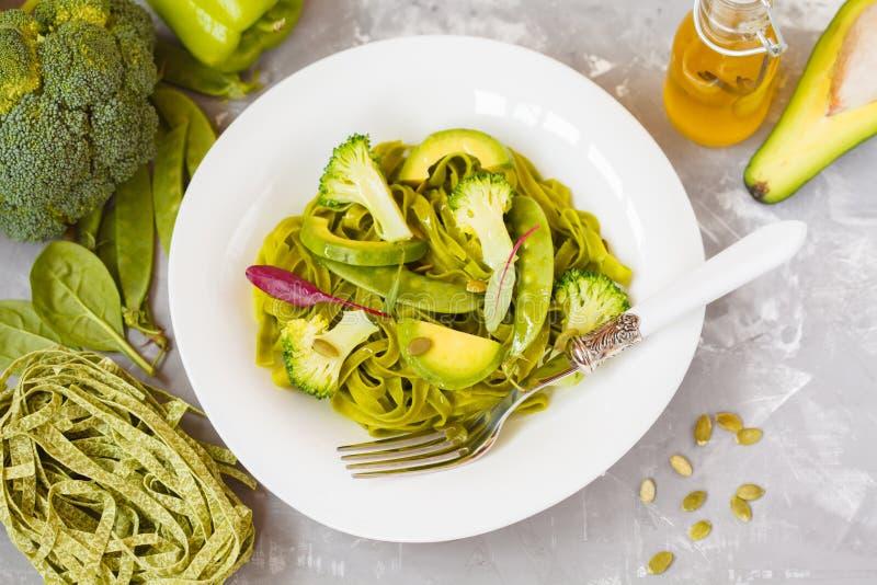 Zdrowy szpinaka makaron z brokułami, avocado, dyniowi ziarna i obrazy stock