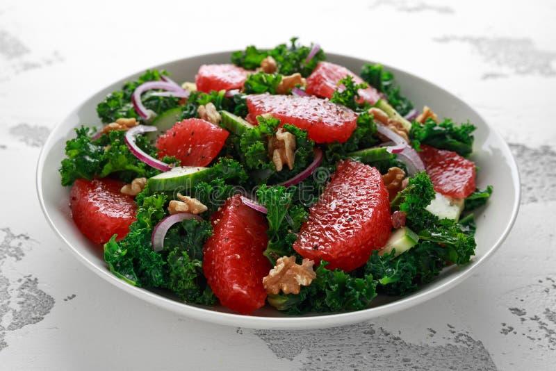 Zdrowy weganin, jarska Grapefruitowa kale sałatka z orzechami włoskimi, czerwona cebula i ogórek na białym tle, obrazy royalty free