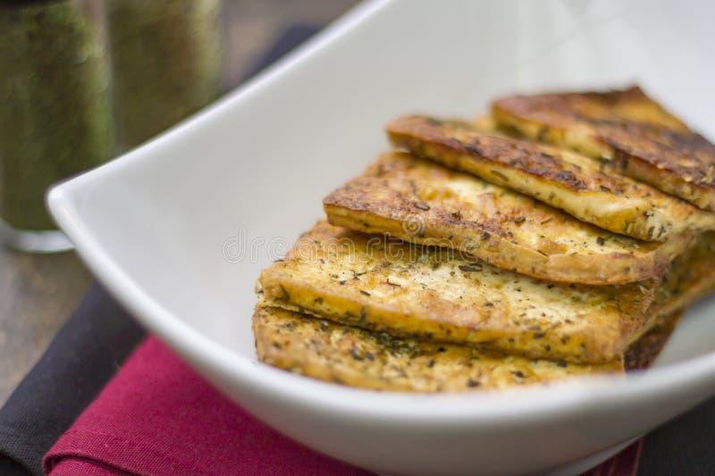 Zdrowy weganin smażył tofu plasterki z seasonings na talerzu zdjęcie royalty free