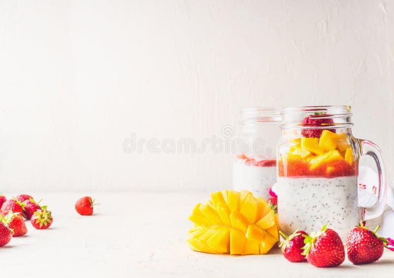 Zdrowy weganinu śniadania tło szkło słoje z chia siają pudding, mango i truskawek na bielu stole jogurtu, kosmos kopii obraz stock