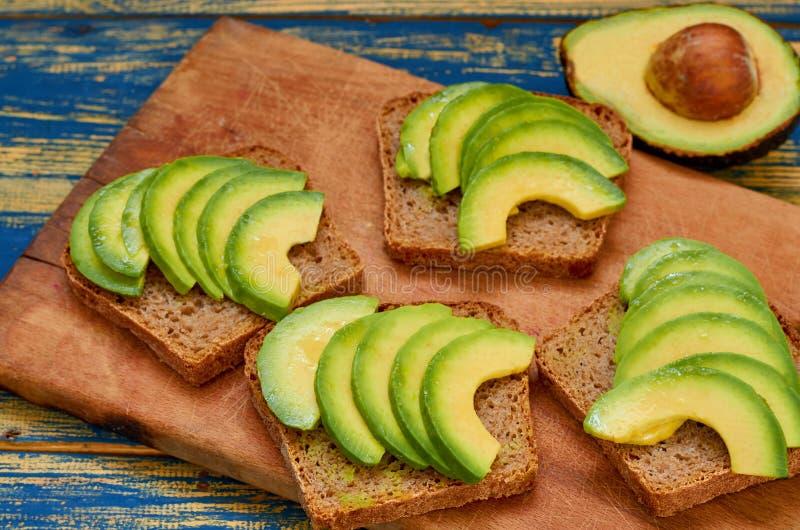 Zdrowy weganinu śniadanie - świeży pokrojony avocado na grzanka chlebie na drewnianej desce fotografia stock