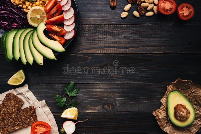 Zdrowy weganinu jedzenia pojęcie Zdrowy jedzenie z warzywami i całej banatki chlebem na drewnianym stołowym odgórnym widoku kosmo zdjęcie stock