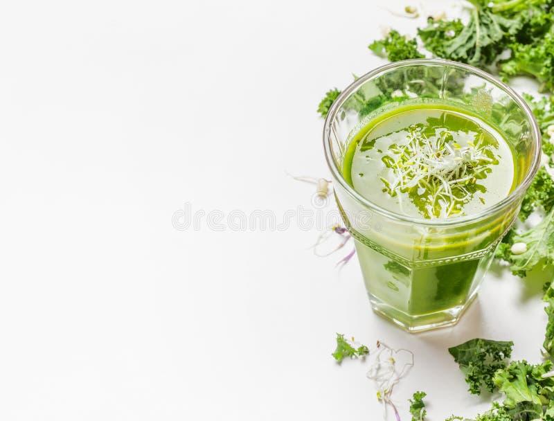 Zdrowy zielony smoothie napój w szkle z kale składnikami na białym drewnianym tle, zamyka up zdjęcie royalty free