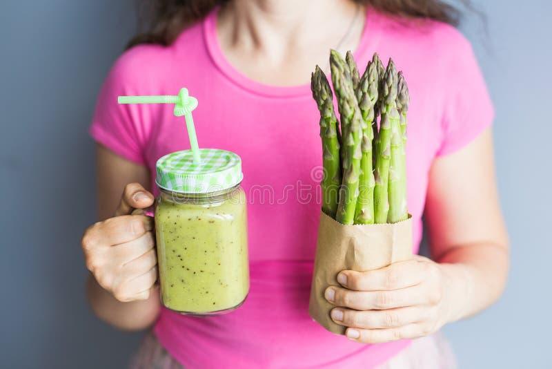 Zdrowy zielony smoothie z asparagusem w kobiety ` s ręce Weganin, surowy jedzenie, detox i dieta styl życia, obrazy royalty free