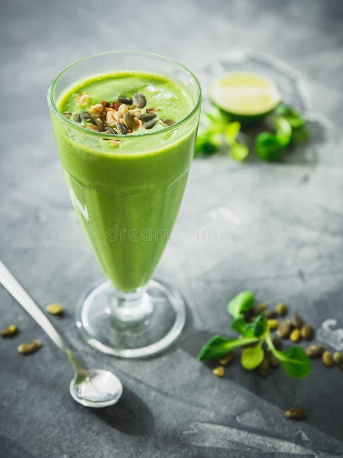 Zdrowy zielony smoothie z szpinakiem, bananem i dyniowymi ziarnami, zdjęcie royalty free