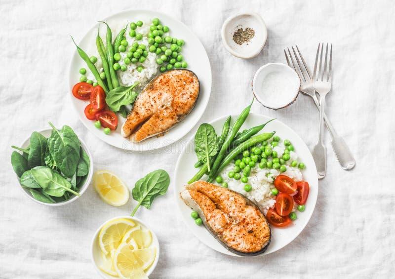 Zdrowy zrównoważony śródziemnomorski dieta lunch piec łosoś, ryż, zieleni grochy i fasolki szparagowe na lekkim tle -, odgórny wi fotografia stock