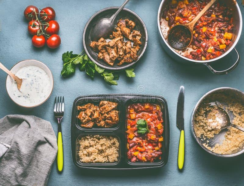 Zdrowy zrównoważony lunchu pudełka przygotowanie z quinoa, pomidor fasolami kumberland i kurczaka mięsem na kuchennego stołu tle, zdjęcie royalty free