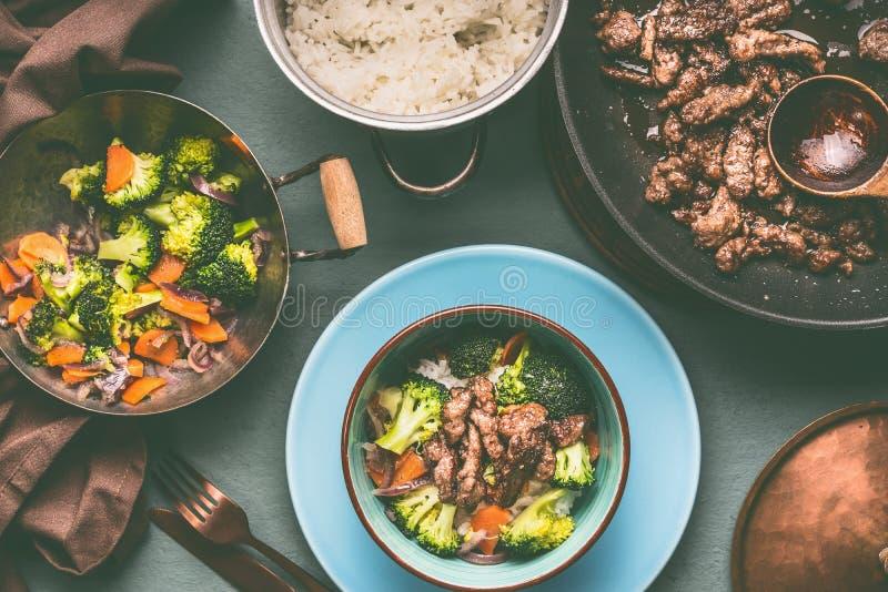 Zdrowy zrównoważony odżywiania naczynie w garnkach i pucharach z wołowiny mięsem, odparowanymi warzywami i ryż na stołowym tle z, obrazy stock