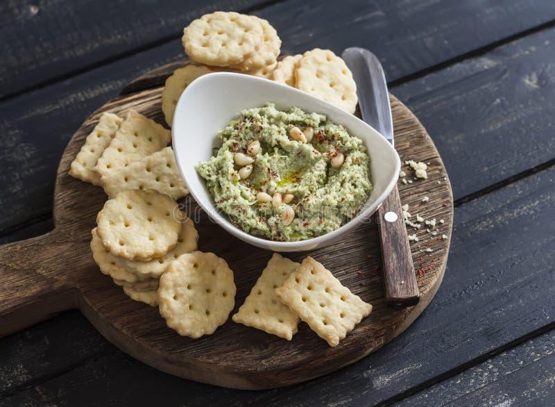 Zdrowych jarskich brokułów i sosnowych dokrętek hummus i domowej roboty serowi ciastka na drewnianym wieśniaku wsiadamy zdjęcie royalty free