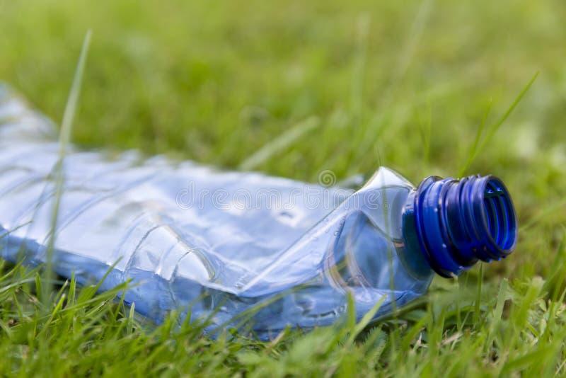 Zdruzgotana błękitna plastikowa butelka kłaść w trawie Zanieczyszczenie i envir fotografia royalty free