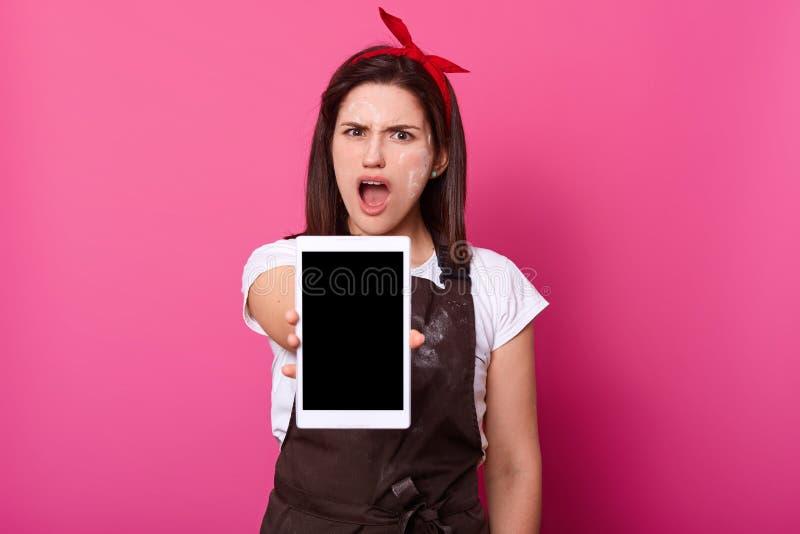 Zdumiewająca kobieta utrzymuje usta szeroko otwarty, chwyt pastylki komputer z czerń pustym ekranem odizolowywającym na różowym t fotografia stock