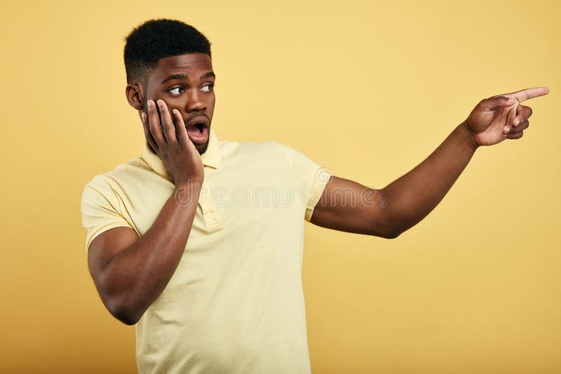 Zdumiewający emocjonalny młody ciemnoskóry mężczyzna ubierał w eleganckiej koszulce zdjęcie stock