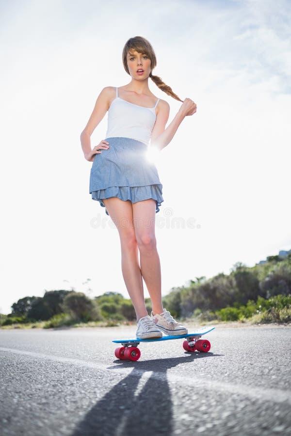 Zdumiewający młodej kobiety równoważenie na jej deskorolka obraz stock