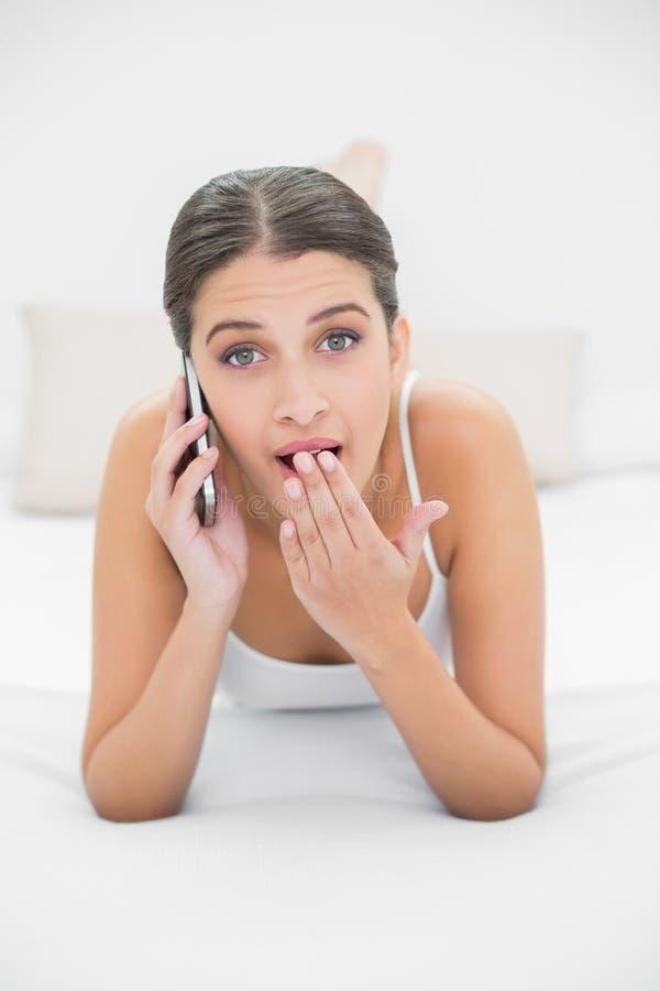 Zdumiewający młody brown z włosami model w białych piżamach robi rozmowie telefonicza obraz royalty free