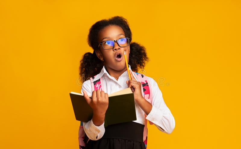 Zdumiona Afrouczennica Robiąca Homework Holding Book I Ołówek, Studio obraz royalty free