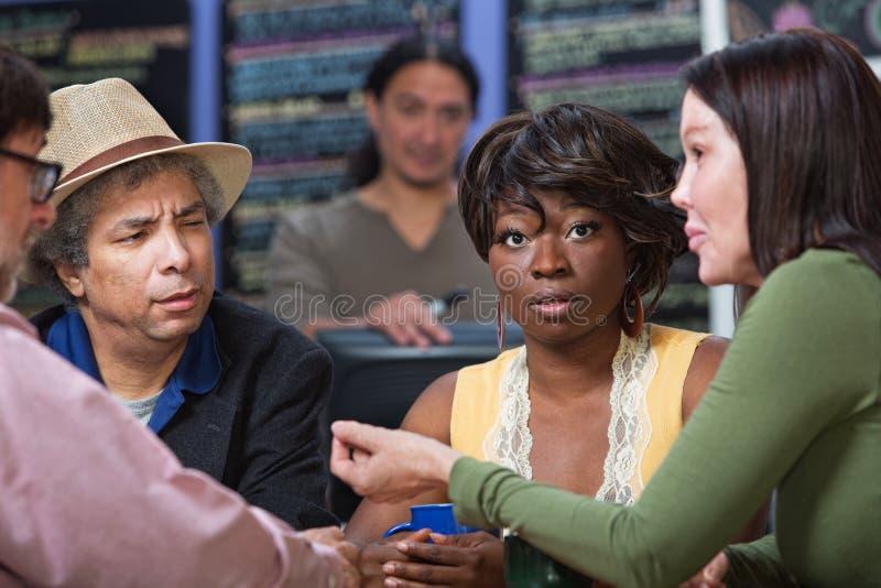 Zdumiona kobieta z grupą w kawiarni zdjęcia stock