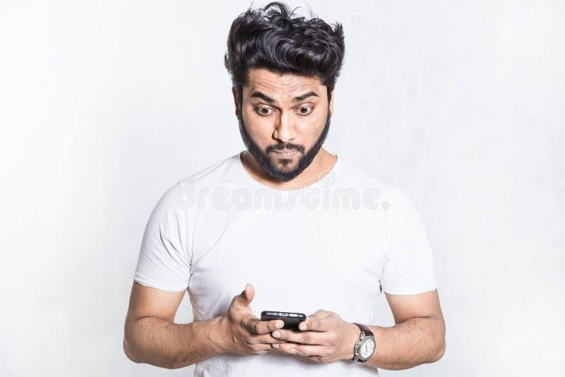 Zdumiony i zmartwiony przystojny młody człowiek trzyma smartphone, gapi się z zdziwionym wyrażeniem fotografia royalty free