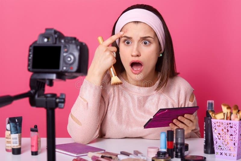 Zdziweni żeńscy blogger cudy i oszałamiają zauważać trądzika na czole, chwyta kosmetyka muśnięcie, gapią się przy kamerą podczas  zdjęcia royalty free