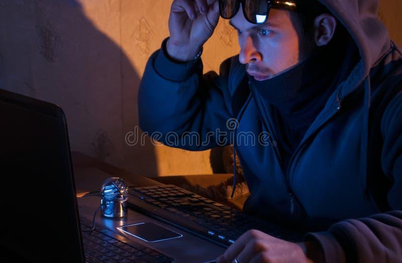 Zdziweni hackerów spojrzenia przy laptopem intruz łamają w system, zdjęcie royalty free
