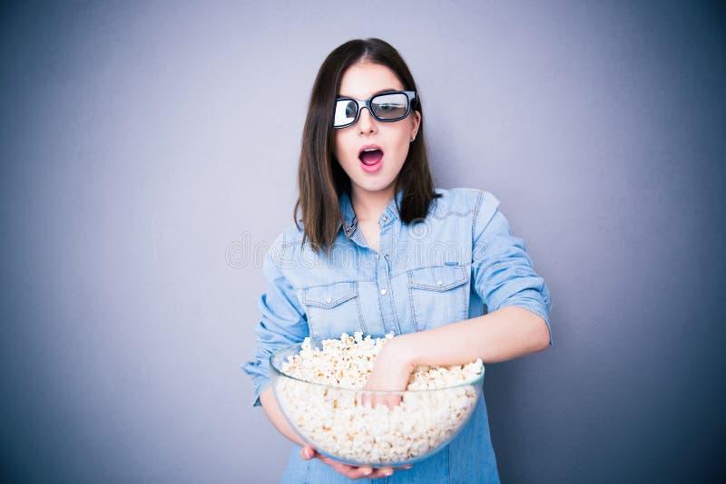Zdziwiona ładna kobieta je popkorn w kinowych glassses fotografia royalty free