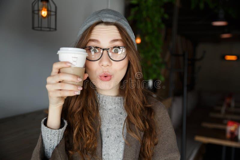 Zdziwiona śliczna młoda kobieta trzyma filiżankę kawy w kawiarni fotografia stock