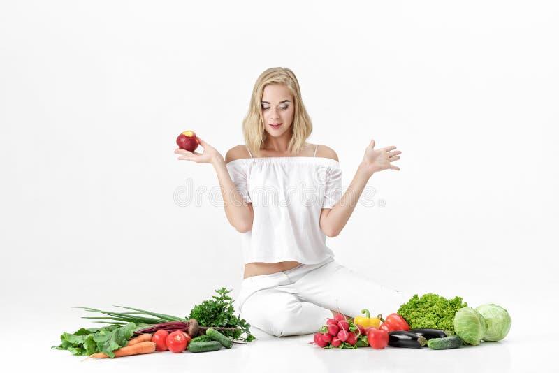 Zdziwiona blond kobieta w biel ubraniach i udziałach świezi warzywa na białym tle dziewczyna je nektarynę zdjęcie royalty free