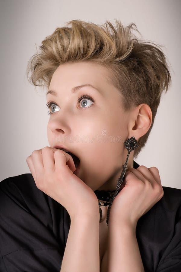 Zdziwiona blond kobieta z usta otwartym i zakrywającym jej ręką obrazy stock