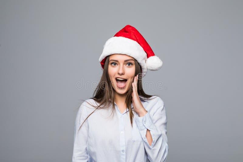 Zdziwiona boże narodzenie kobieta jest ubranym Santa kapeluszowy ono uśmiecha się odizolowywam nad szarym tłem zdjęcia royalty free