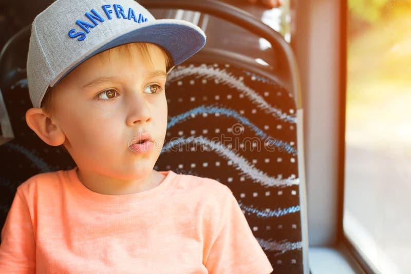 Zdziwiona chłopiec przyglądająca za okno autobus Śliczna chłopiec w nakrętki obsiadaniu w autobusie Podróż, styl życia i ludzie p obraz stock