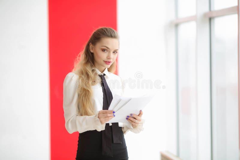 Zdziwiona elegancka dziewczyna trzyma falc?wk? z dokumentami i patrzeje kamer? w biel ubraniach obrazy royalty free