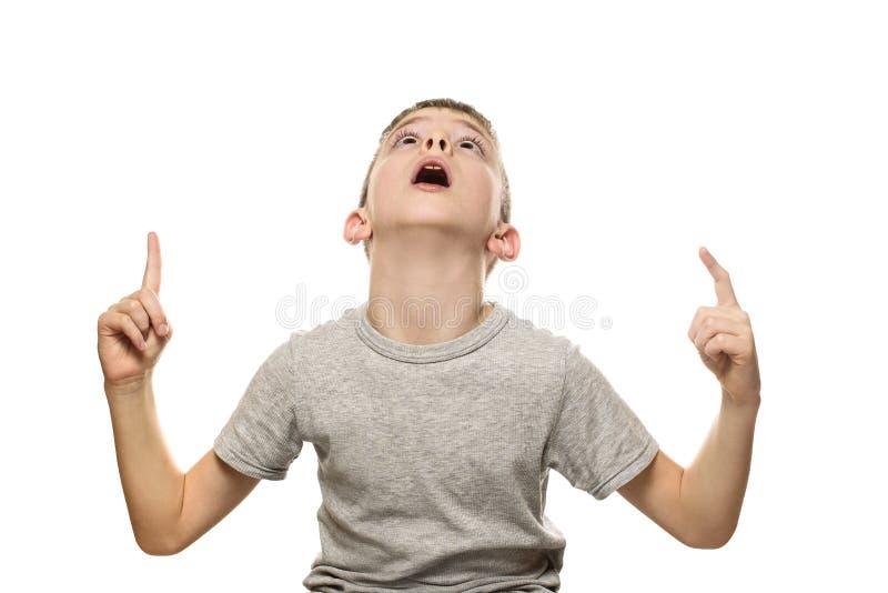 Zdziwiona jasnogłowa chłopiec w koszulki szarych stojakach i punktach z palcami wskazującymi w górę Odizolowywa na białym tle zdjęcie stock