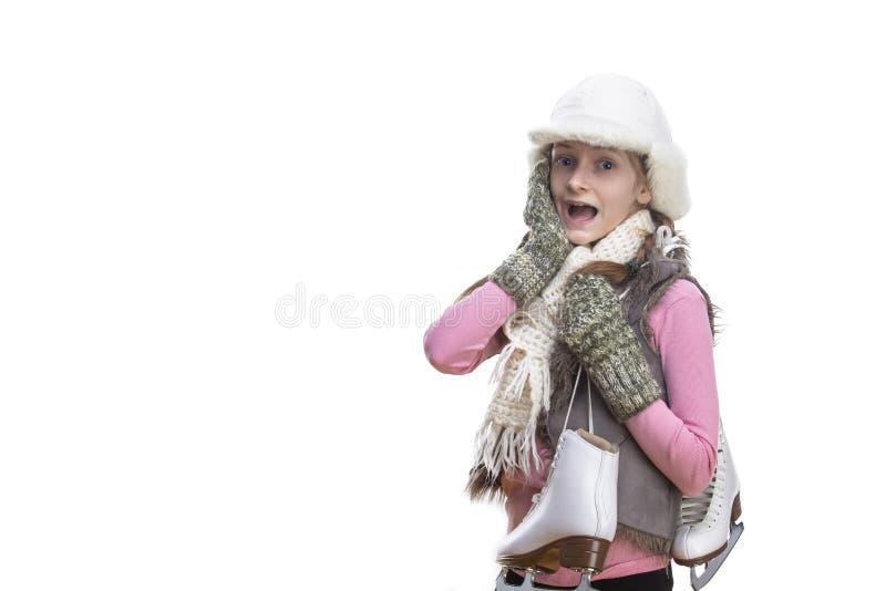 Zdziwiona Kaukaska Blond dziewczyna w zimie Odziewa Pozować obracam z Lodowymi łyżwami Nad ramieniem W rękach W przodzie przeciw zdjęcia stock